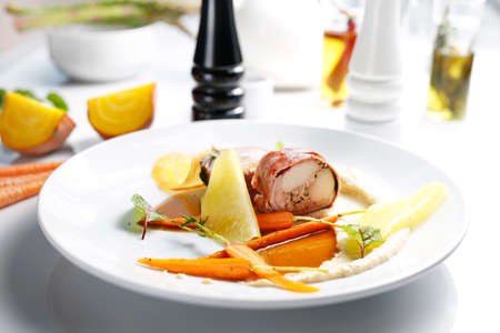 Rabbit roulade with prosciutto ham, celery puree and carrot glazed. A gourmet dish on a white plate. Food photography. The chef serves the dish.