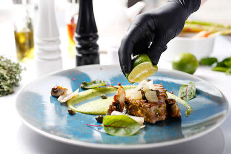 Grilled tuna steak with pistachio nuts, capers and green peas. Tasty dish on a blue plate. Food photography. The chef serves the dish. 版權商用圖片