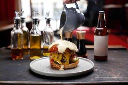 Burger with cheese sauce. A classic chamburger with cheese chedar, bacon and vegetables poured cheese sauce. Culinary photography. Proposal for dishes. 版權商用圖片