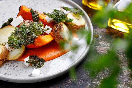 Baked vegetables on pumpkin puree. Vegetarian cooking. Culinary photography. Suggestion to serve the dish.