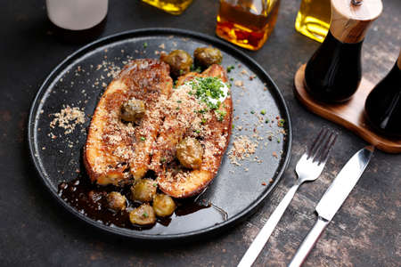 Baked eggplant steak with Brussels sprouts. Culinary photography. Suggestion to serve the dish.