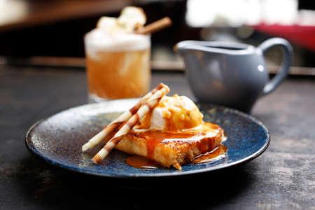 Apple pie with vanilla ice cream and caramel sauce. Appetizing sweet dessert. Culinary photography.
