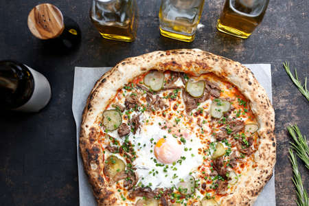 Pizza with egg, pulley pork, pickles and cheese. Culinary photography. Proposal for dishes.