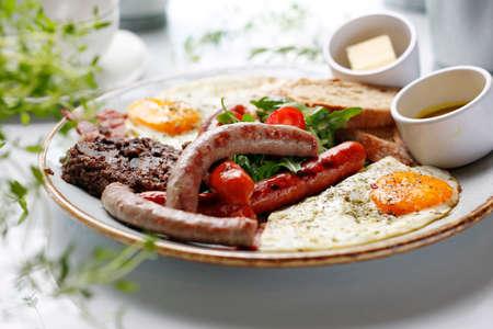 Breakfast. Fried eggs, fried sausages, black pudding, salad.