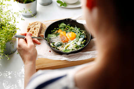 Shakshouka, eggs baked with green peas and spinach. Baked eggs with green peas and spinach. nutritious healthy breakfast. Ready dish served in a hot pan. Suggestion of serving the dish.