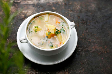 Vegetable soup, healthy soup made of fresh vegetables. Home cooking. vegetarian. Dish in a plate on a dark background.