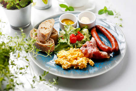 Continental breakfast, scrambled eggs, fried sausage, bacon and vegetable salad. Ready dish served in plate. Suggestion of serving a dish on a plate. food background Standard-Bild