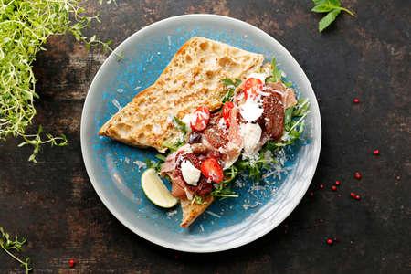 Sandwich with ripening ham, Parmesan cheese, sun-dried tomatoes, green salad. Ciabatta with ripening ham, Parmesan cheese, sun-dried tomatoes, green salad. Italian breakfast Standard-Bild