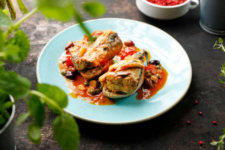 Stewed mackerel in tomato sauce with capers served on toast. Mackerel baked in tomato sauce with capers. Suggestion of serving a dish on a plate. food background