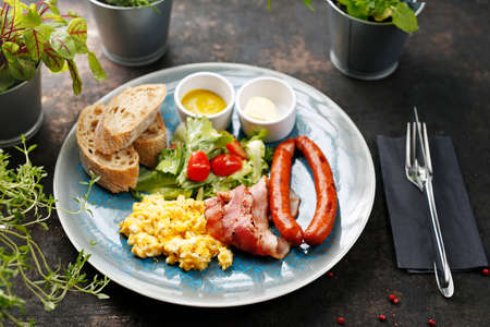 Breakfast, scrambled eggs, fried sausage and vegetable salad. Continental breakfast. Suggestion of serving a dish on a plate. food background