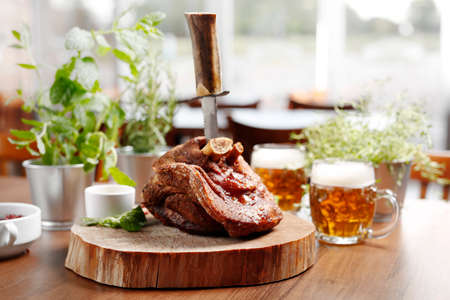 Pork knuckle baked in beer. A nutritious portion of meat. Baked pork knuckle in Bavarian style. Suggestion of serving a dish on a natural desk. food background