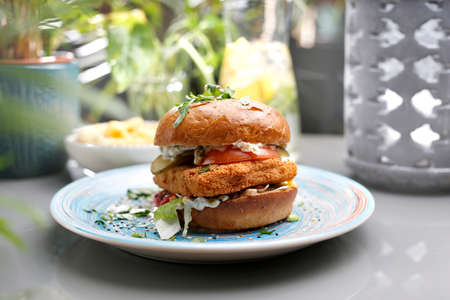 Vegetarian burger with tofu cheese and vegetables. A colorful appetizing dish. Culinary photography, food styling. Standard-Bild