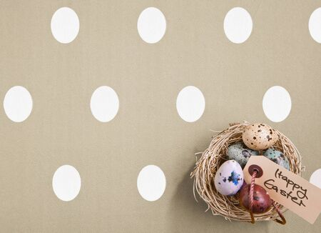 Small nest containing colored eggs over a Easter concept background photo