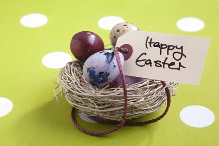Colored eggs in a small nest with a Happy Easter tag photo