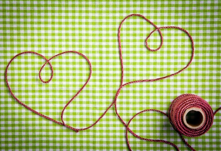 string together: Hearts drawn with purple thread through a tag over a checkered fabric pattern Stock Photo
