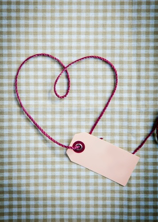 Heart drawn with purple thread through a tag over a checkered fabric pattern photo