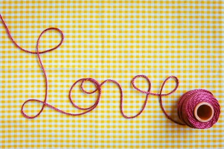 forgiven: The word love drawn out with purple thread and a checked fabric background.