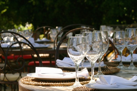 Banquet table in South afrika with glasses and napkins under a big tree