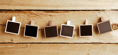 Six Squary Polaroid-style photo frames in a row on a wooden background