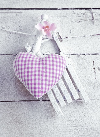 A pretty romantic checked violet needlework heart with flower hanging on painted white boards photo