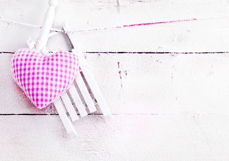 wintery day: Romantic checked snowy needlework heart for Valentines hanging on snow white boards with copyspace