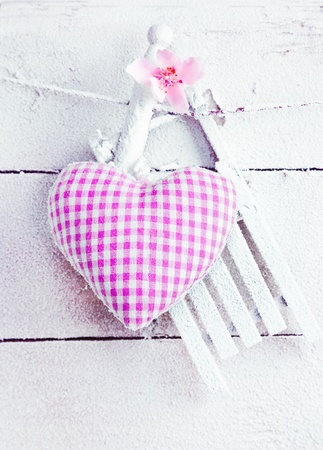 Romantic checked snowy needlework heart for Valentines hanging on snow white boards with copyspace Stock Photo - 12301301