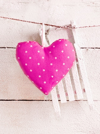 Romantic checked pink needlework heart for Valentines hanging on snow white boards with copyspace photo