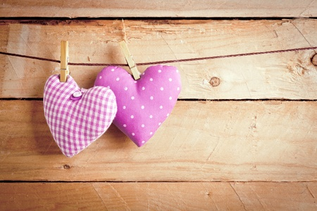 peg board: Two pretty pink material Valentine hearts hanging on a line with clothes pags over wooden boards.