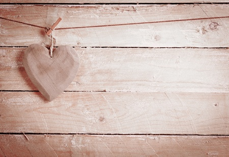 Quaint rustic wooden heart hanging from a peg against wooden boards with copyspace in a concept of love and romance,
