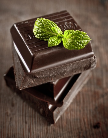 stack of chocolate pieces with a leaf of mint on wooden background photo