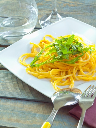 Plate of delicious pasta topped with fresh herbs served ready for dining. photo