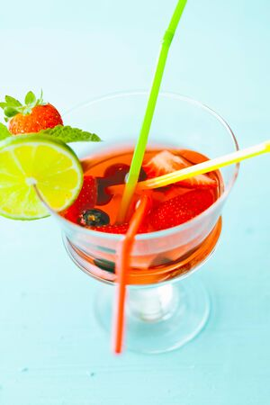sangria with colored straws and strawberries in a glass photo