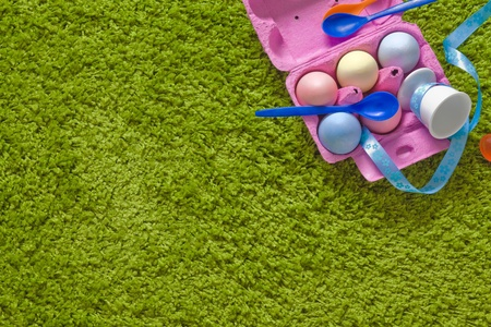 eastertime: colored easter eggs and spoons in a egg-box on green background