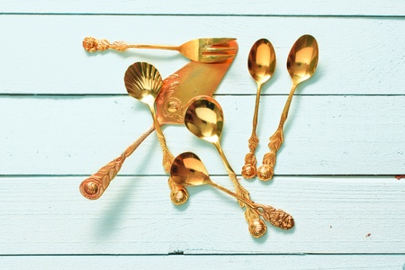 golden pastry fork, cake lifter, sugar spoons on a light blue wooden plate photo