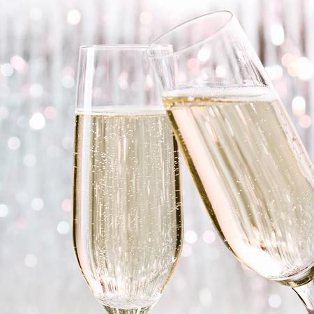 dwarsfluit: Twee elegante fluiten mousserende witte champagne met veel bubbels op feestelijke achtergrond, viering concept. Stockfoto