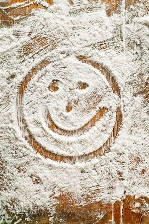 Flour Artwork With Food And Handprints, Fun background with the sign SMILEY and human handpints in scattered flour on a wooden tabletop. photo