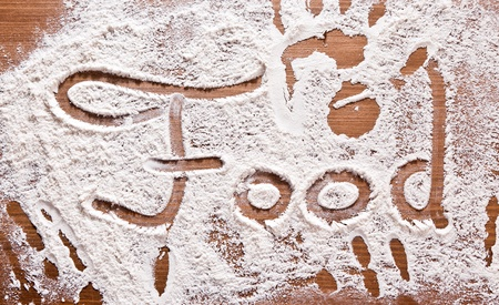 Flour Artwork With Food And Handprints, Fun background with the word FOOD and human handpints in scattered flour on a wooden tabletop. photo