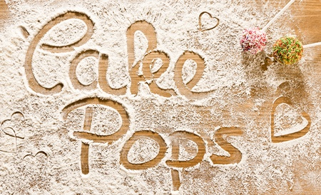 Flour Artwork With Food And Handprints, Fun background with the word Cakepops and human handpints in scattered flour on a wooden tabletop. photo