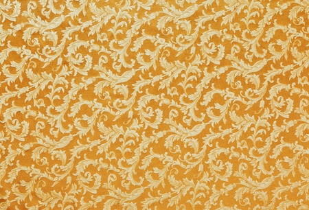 Abstract background of a heavy golden brocade fabric with interwoven repeat design. Imagens