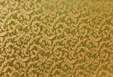 Abstract background of a heavy golden brocade fabric with interwoven repeat design. photo