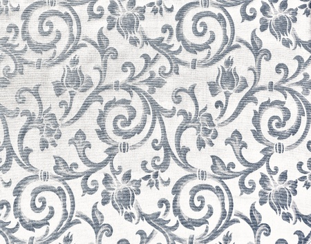 Abstract background of a heavy grey brocade fabric with interwoven repeat design.