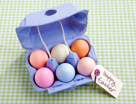 egg carton: Egg carton with different colored Eggs. On a green checked background with a handwritten memo Happy Easter Stock Photo