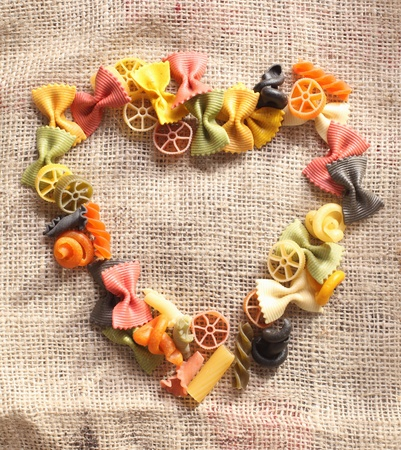Colorful beauty Pasta Heart. Heart-shaped arrangement of colourful bowtie pastas, or farfalle, on rustic hessian material, concpetual of love and romance. Stock Photo - 12301765