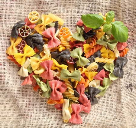 Colorful Bowtie Pasta Heart. Heart-shaped arrangement of colourfaul bowtie pastas, or farfalle, on rustic hessian material, concpetual of love and romance. photo