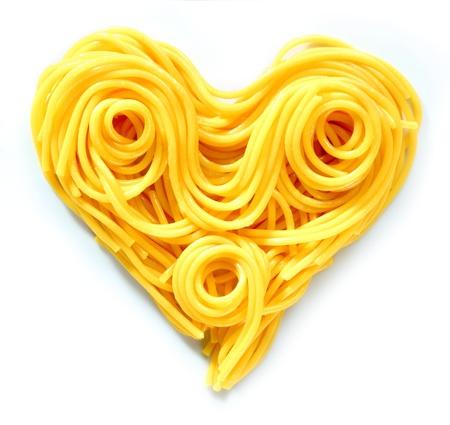 maccheroni: Beauty Pasta Heart. Heart-shaped arrangement of pasta, or spaghetti, isolated on white, concepetual of love and romance. Stock Photo