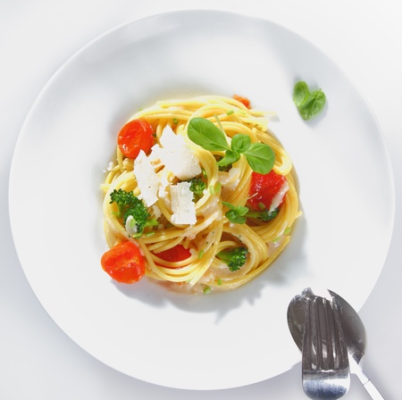 brocoli: Overhead view of a prepared plate of spaghetti broccoli with parmesan ready for serving garnished with tomatoes and basil Stock Photo