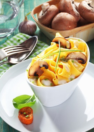 ribbon pasta: Boat-shaped dish of mushroom tagliatelle with a bowl of fresh mushrooms in the background. Stock Photo