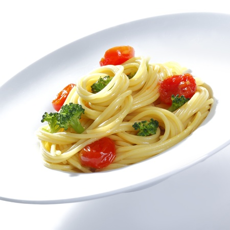 A prepared plate of spaghetti broccoli ready for serving garnished with tomatoes and basil photo