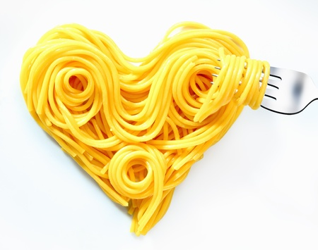 Cooked plain spaghetti coiled and looped into a heart shape symbolic of Valentine, romance and love. photo