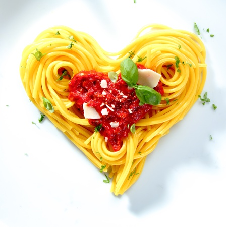 Spaghetti with tomato and cheese sauce garnished with basil arranged in coils into a heart shape for love,